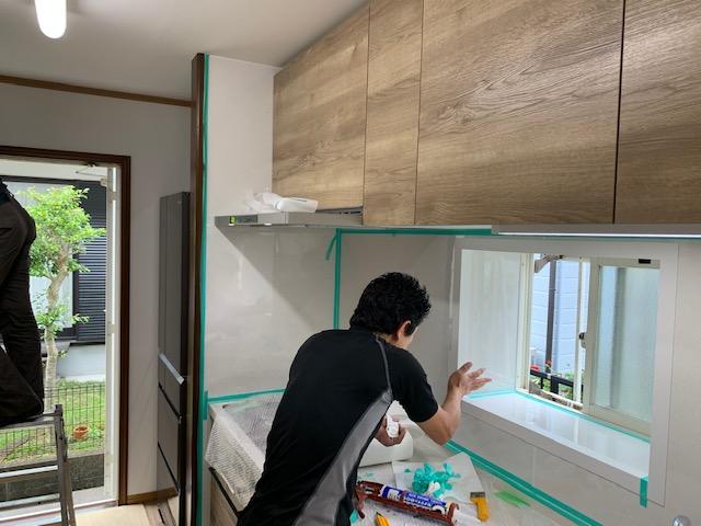 キッチンパネルを貼りコーキングを打つ状況
